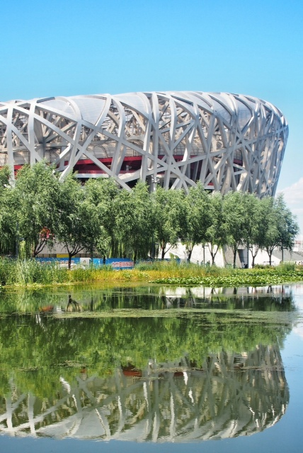 On the way back to Beijing, we decided to stop to see the Birds Nest stadium, and the water cube. The stadium itself looks suitably futuristic, with it's silver-gray lattice exterior and is an imposing venue. There were a surprising amount of people milling around the area, or just sitting in shaded areas. But these were seemingly outnumbered by the refreshment sellers, or the hawkers selling kites and plastic wind up toys. Unfortunately the stadium suffered from that same affliction that all stadiums do on none event days as it was lifeless without the noise and buzz of excitement that a match day brings. The Nest appears to suffer more than most in this, for in the harsh sunlight the open framework of the exterior allows you see int the inner working of the generators and air conditioning that would ordinarily be disgusted by the dark, and the coloured floodlights. It remains however, an impressive venue. In the evening a few of us went out to dinner together to a place nearby our hotel. We had sticky rice, beef, dumplings, veg and more of the chicken with peanuts that seems so popular. It is fantastic to be eating with company again, as just having a little conversation during a meal makes such a difference. In the evening, we all went to the theatre to watch an acrobatics display. This was excellent and we watched as the performers twisted and turned into all kinds of impossible shapes, eliciting gasps from the audience. One particular woman performer was incredible. She would balance atop a tiny platform on one arm, and then proceed to contort and twist into all manner of painfully looking positions. At one point she had brought both legs over her back and then crossed her feet below her chin, again whilst balanced on one arm and perched atop a platform not much bigger than her handspan! Half the time we in the audience didn't know whether to applaud or to stay silent for fear of breaking the performers concentration. The performance itself wasn't flawless with